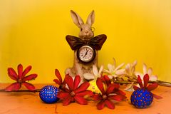 Easter bunny with a clock on his chest surrounded by spring flowers with blue, yellow and white eggs stock image