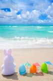 Easter bunny and color eggs on the beach Stock Photo