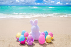 Easter bunny and color eggs on the beach Stock Photos