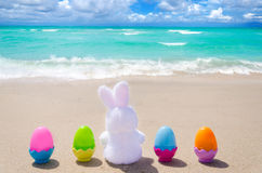Easter bunny and color eggs on the beach Stock Images