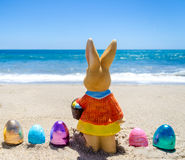 Easter bunny with color eggs on the ocean beach Royalty Free Stock Photos