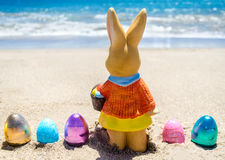 Easter bunny with color eggs on the ocean beach Stock Images