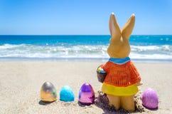 Easter bunny with color eggs on the ocean beach Stock Photos