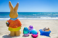 Easter bunny with color eggs on the ocean beach Stock Photo