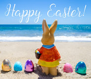 Easter bunny with color eggs on the ocean beach Royalty Free Stock Images