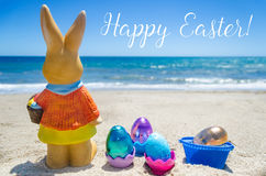 Easter bunny with color eggs on the ocean beach Stock Photography