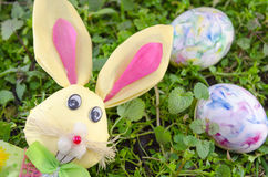 Easter bunny and a colored egg on the grass Royalty Free Stock Image
