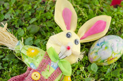 Easter bunny and a colored egg on the grass Royalty Free Stock Photos