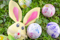 Easter bunny and a colored egg on the grass Royalty Free Stock Images