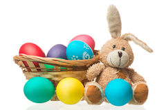 Easter bunny and colored eggs in a basket on a white background Royalty Free Stock Photo