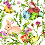 Easter bunny, colored eggs in grass and flowers with butterflies. Seamless floral easter pattern with egg hunt Royalty Free Stock Photography