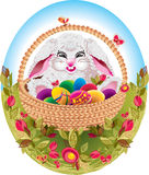 Easter. Bunny with colorful eggs in a basket, on the grass Royalty Free Stock Images