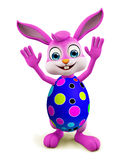 Easter Bunny with colorful eggs saying hi pose Royalty Free Stock Image