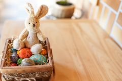 Easter bunny and colorful eggs in the basket on wood background. place for text . happy easter celebration card royalty free stock image