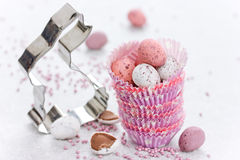 Easter bunny cookie cutter and chocolate candy mini eggs in pape Stock Photography