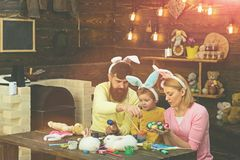 Easter bunny costume. Mother, father and child painting Easter eggs. Easter bunny costume. Mother, father and her child enjoy painting Easter eggs stock images