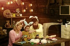 Easter bunny costume. Mother, father and child painting Easter eggs. Easter bunny costume. Mother, father and her child enjoy painting Easter eggs stock image