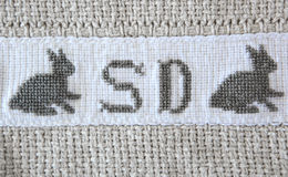 Easter bunny Cross-stitch on cotton blanket. English Initials and bunny embroidered on grey cotton blanket using cross -stitch  embroidery technique Royalty Free Stock Image