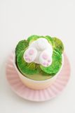 Easter bunny cupcake. Cupcake with a fondant Easter bunny topper. Bunny is digging in fondant salad with his and feet sticking out royalty free stock photo