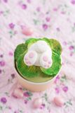 Easter bunny cupcake. Cupcake with a fondant Easter bunny topper. Bunny is digging in fondant salad with his and feet sticking out royalty free stock photos