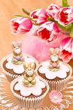 Easter Bunny Cupcakes. Little Easter bunny cupcakes on glass stand with spring tulips Royalty Free Stock Image
