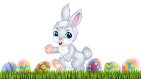 Easter bunny with decorated Easter eggs in a field Stock Photos