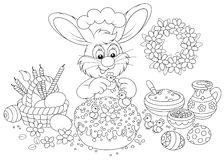 Easter bunny decorates a cake. Rabbit decorating an Easter cake to the upcoming holiday, black and white outline illustration for a coloring book Stock Photo