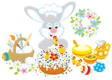 Easter bunny decorates a cake. Grey bunny decorating a colorful Easter cake to the upcoming holiday Royalty Free Stock Photography