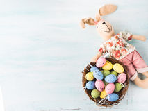Easter bunny doll quail painted egg nest pastel backdrop Stock Image