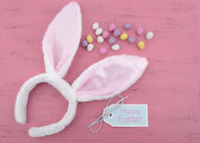 Easter bunny ears with Easter eggs on pink wood Stock Photos
