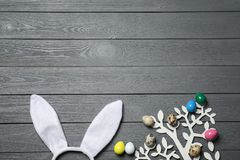 Easter bunny ears headband and decorative tree with colorful eggs on wooden background, flat lay. Space for text stock image
