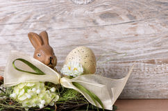 Easter bunny with easter egg in the nest. Against wooden background as an Easter greeting with free text space Royalty Free Stock Photos