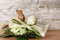 Easter bunny with easter egg in the nest. Against wooden background as an Easter greeting with free text space Royalty Free Stock Images