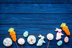 Easter bunny and easter eggs cookies. Easter symbols and traditions. Blue wooden background top view copy space. Easter bunny and easter eggs cookies. Easter Royalty Free Stock Images