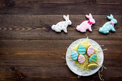Easter bunny and easter eggs cookies. Easter symbols and traditions. Dark wooden background top view copy space. Easter bunny and easter eggs cookies. Easter Royalty Free Stock Photo