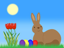 Easter Bunny with Easter Eggs and tulip on grassland Stock Photos