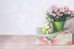 Easter bunny with egg, pink snowdrops in a pot and green box on Royalty Free Stock Photos