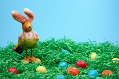 Easter Bunny with eggs. In grass on blue  background Royalty Free Stock Images