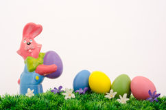 Easter bunny and eggs. Easter bunny and colored eggs on green meadow with flowers Stock Photography