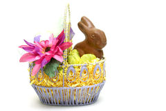Easter bunny with eggs. Easter bunny with chocolate eggs and flowers  in a basket isolated on white background Stock Photography