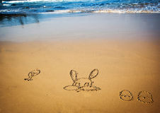 Easter bunny and eggs drawn in sand Stock Images