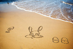 Easter bunny and eggs drawn in sand Royalty Free Stock Photos