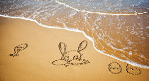 Easter bunny and eggs drawn in sand Stock Photos