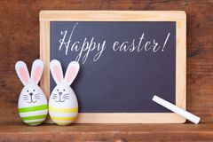 Easter bunny eggs with ears and chalkboard royalty free stock image