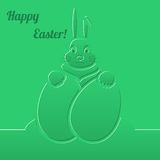 Easter bunny with eggs. Green paper background. Royalty Free Stock Image