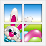 Easter bunny with eggs looking by the window Stock Photos