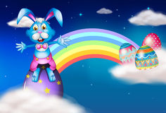 An easter bunny and eggs near the rainbow Royalty Free Stock Photo