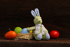 Easter Bunny Eggs on Rough Background. Easter Bunny Toy with colorful eggs in natural raffia nest on rough dark wooden background, copy space Stock Images