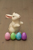 Easter Bunny with Eggs. White ceramic Easter Bunny up on hind legs sitting with four pastel sparkly Easter eggs on a wood surface Royalty Free Stock Image