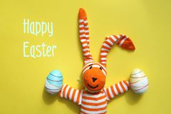 Easter bunny and eggs on yellow background. stock photos